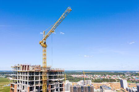 multistorey apartment building under construction. yellow crane near the building against blue sky