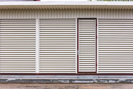 exterior view of warehouse with locked door. metal sheet louvers on wall for ventilation