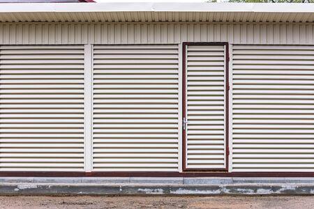 Vista exterior del almacén con puerta cerrada. rejillas de chapa metálica en la pared para ventilación