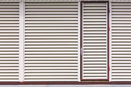 entrance door in the storehouse building. metal sheet louver with horizontal bars on the wall Banco de Imagens