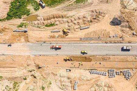 roadrollers and grader flattening the ground before road construction. aerial view