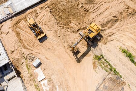 aerial top view of yellow industrial heavy machines moving ground at construction site