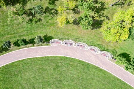 park landscape in summer time with trees, green lawn, benches and footpath. aerial top view