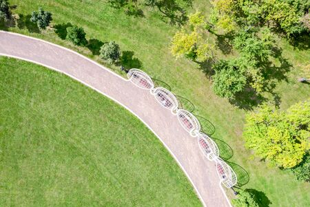 aerial top view of city park summer landscape with trees, green lawn and walking path