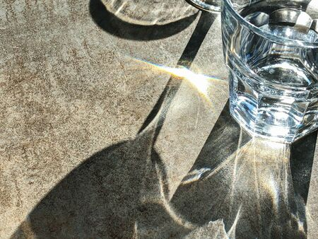sunlight shine through glass. beautiful light and shadow on stone surface of table