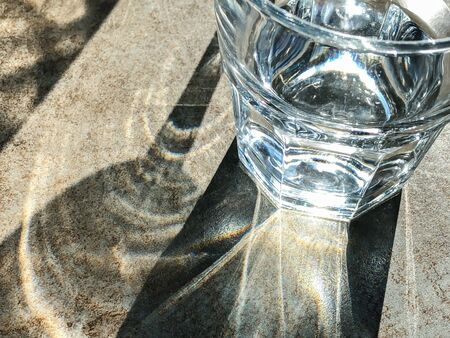 shadow of glass of water reflected sun light against light brown background