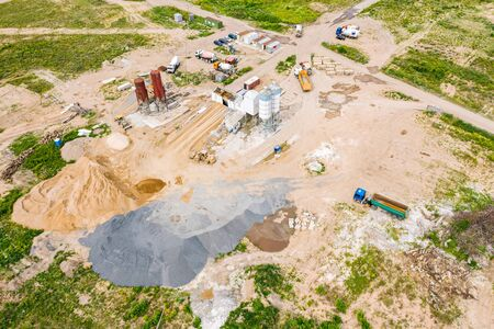 aerial image of city construction site. cement processing facility and various building machines and equipment