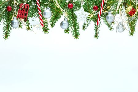 new year holiday white background with christmas tree branches, various decorations and glowing light garlands