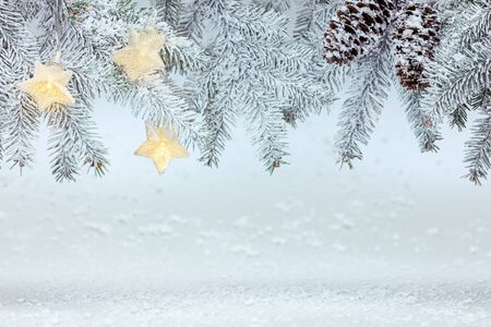 fir tree branches with cones under snow with star lights garland. new year background 免版税图像