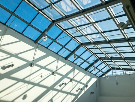 view from below the transparent glass roof of shopping mall at sunny day Foto de archivo