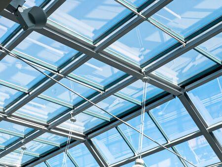 primer plano vista interior del techo de cristal transparente moderno. cielo azul a través de un techo de cristal