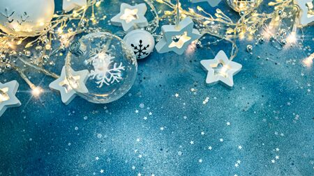 beautiful christmas tree balls and shining star lights on blue background with silver confetti Stock Photo
