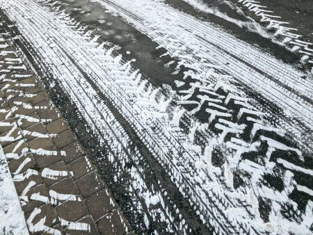 asphalt with snowy tires imprints. textured winter background
