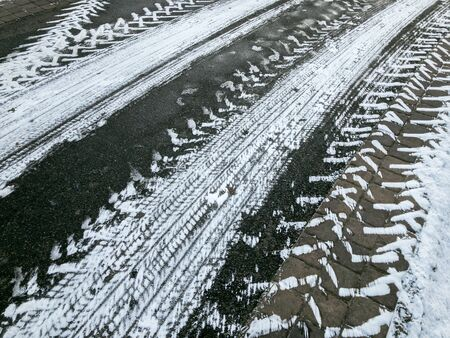 tyre traces imprints on asphalt road. winter season. abstract snowy texture