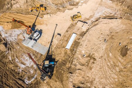heavy construction machinery working in construction site. aerial photo from flying drone