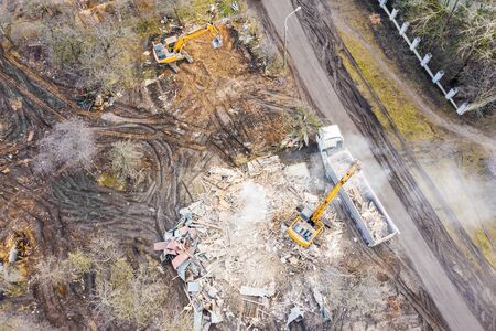 excavator on pile of debris of a destroyed building, loading dump truck. aerial view from the drone
