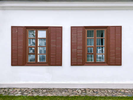 row of classical wooden windows with shutters on white building facade wall