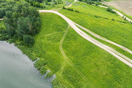 countryside landscape in summer. rural dirt road on green meadow near lake. birds eyes view Archivio Fotografico
