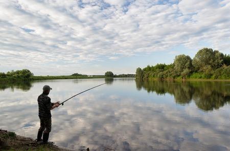 pescador: La pesca en river.A pescador con una caña de pescar en la orilla del río. Hombre pescador captura un pez Foto de archivo