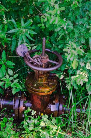 soggy: old leaked  rusty country water supply system with chain and lock