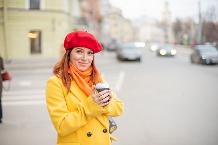 The red-haired young woman in a yellow coat and red beret is drinking coffee on the street to keep warm