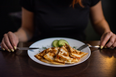 Woman eating delicious quesadilla in restaurant. Young redheaded woman is eating Mexican food in a cafe Stock Photo
