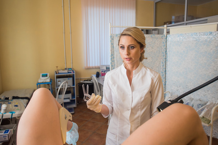Friendly female blonde hair doctor gynecologist is working with patient.