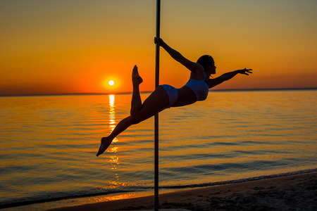 Athletic girl stands next to a portable pylon on the beach. Sand, sunset, beach.