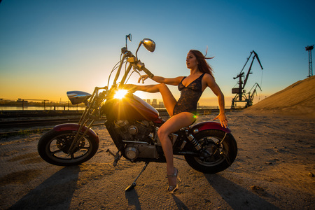 Red-haired woman in lingerie in high heels sits on a motorcycle. Attractive red-haired girl sits on a motorcycle at sunset on the background of the industrial landscape