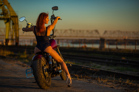 Red-haired woman in sexy lingerie in high heels sits on a motorcycle. Attractive red-haired girl sits on a motorcycle at sunset on the background of the industrial landscape Stok Fotoğraf