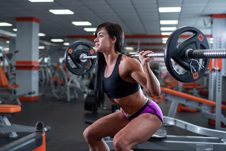 A strong, muscular dark-haired girl performs squats with a light barbell. Gym