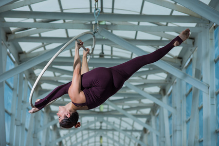 An air gymnast makes a Russian splits on an air hoop suspended on a metal truss. circus actress on the airy ring.