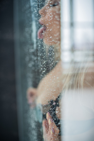 European girl in black underwear, pressed her chest and hands to the wet glass and erotic licking tongue drops.