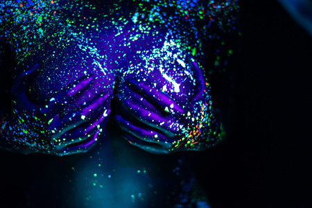 Ultraviolet body art blue night sky with stars. Fluorescent paint on a large female covered with hands