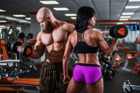 Powerful, muscular, strong, man and woman, pick up the dumbbell with your hands. Nice bicep. They look in different directions. 写真素材