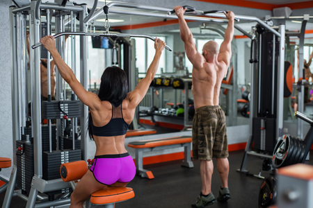 Powerful, muscular, strong, guy and girl, train back. The guy performs pull-UPS, the girl makes a craving for the head.