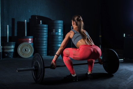 Young, European, muscular girl in red leggings, doing exercise with a barbell in the gym for crossfit. Dark background. Imagens