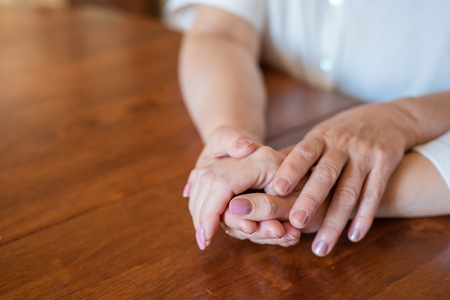 Elderly mother and her daughter holding hands while sitting at the table.Close up on women of different generations holding hands. Close Up Shot Of Mother And Daughter's Hands Holding.