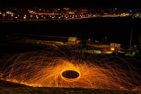 Large round burning fireworks sparkle from the burning steel wool. The city lights at night