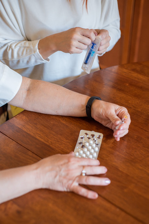 Elderly woman holds pills and ampoule. Close-up of pensioners hands with drugs. Young woman unpacks the syringe. Daughter is going to give an injection to an elderly mother.