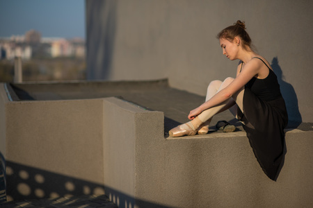 Ballerina in a tutu posing near the fence. Beautiful young woman wearing a black dress and wearing pointe shoes outside. Gorgeous ballerina demonstrates amazing stretching.