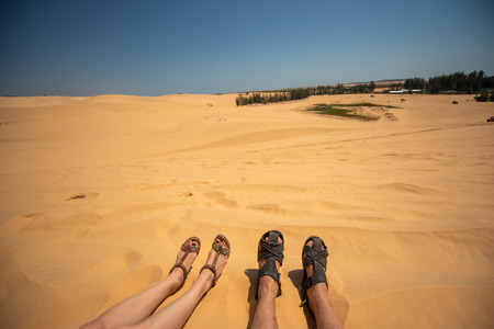 Close up portrait of legs,  legs of couples lying with a mixture of golden sand dunes.Feet of a man and a woman in sandals on the sand, Vietnam. Desert.
