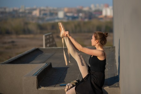 Ballerina in a tutu posing near the fence. Beautiful young woman wearing a black dress and wearing pointe shoes outside. Gorgeous ballerina demonstrates amazing stretching 免版税图像