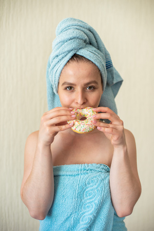 The girl in a towel has breakfast in the bed. A young attractive woman eats donuts in bed. The girl with a towel on her head happily eats donuts