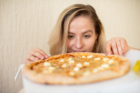 Porträt einer Frau, die Pizza isst. Schöne junge Frau in schwarzer Unterwäsche, die Pizza isst.