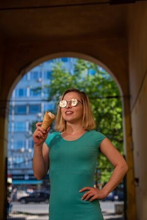 A happy woman in a turquoise dress stands in an arched passage and eats a waffle cone on a warm summer day. Beautiful blonde in sunglasses enjoys ice cream while walking. Summer dessert Standard-Bild