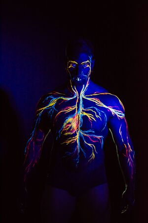 UV picture of the circulatory system body art on the body of an adult male. On the chest of a muscular athlete, veins and arteries are drawn with fluorescent dyes. Neon light 스톡 콘텐츠