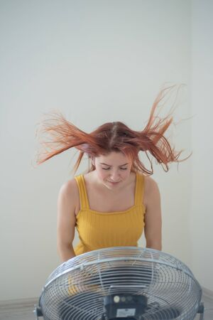 Portrait of a beautiful red-haired woman in a mustard jumpsuit enjoying the cooling breeze from a large electric fan. A smiling girl freshens up in the hot summer heat. Hair develops from the wind