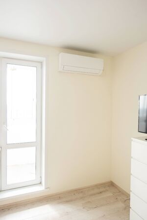 The air conditioner is installed in the corner of the real room next to the door to the balcony. The interior of the bedroom 版權商用圖片