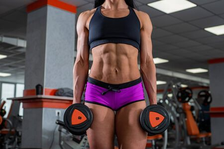 A powerful, strong, muscular girl with beautiful abdominal muscles holds dumbbells in her hands.
